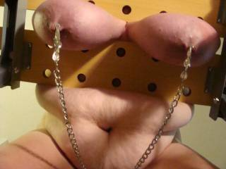Chained to bench with tits inclamp and clamps on nipples