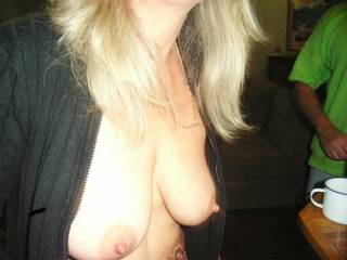 tits hanging out with a guy behind her wanting to grope her at a party