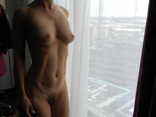 Naked by the hotel room window