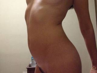 Striking a pose showing small tits and trimmed pussy