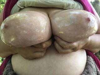 Holding together her lovely big oiled tits in woodland