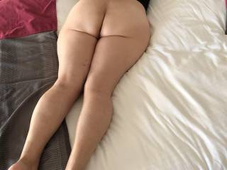 A very nice view of her behind laying on hotel bed.