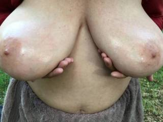 With her big tits already oiled, my friend gives them a workout in woodland