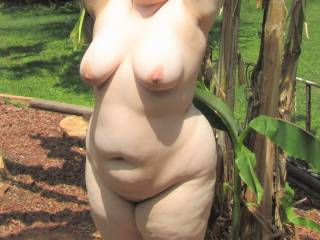 My wife naked in the garden showing off her chubby curves for the camera. The neighbours would've gotten a show had they looked outside!