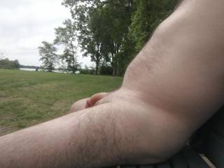 Naked outside on a park bench.