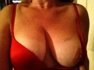 "Your not fooling me cutie ;) we know you tagged it to show it off. BTW you look simply delicious in Red, this bra especially looks made for you. Now that we caught you ""Red"" handed being a naughty tease, go ahead and let your inner Slut-MILF out to play ;). Pull that other lovely breast out for display, wrap one arm under them as you tease around your panties with your other hand giving us sensory overload =) Please? ;)."